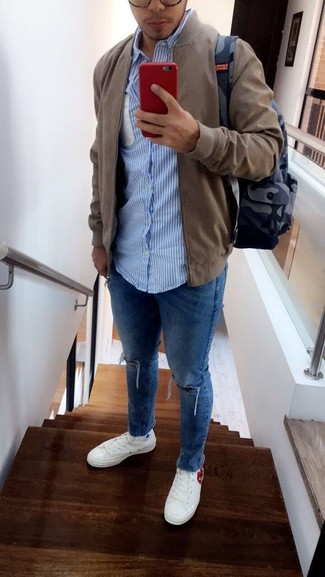 How to wear: white canvas low top sneakers, blue ripped skinny jeans, light blue vertical striped long sleeve shirt, olive bomber jacket