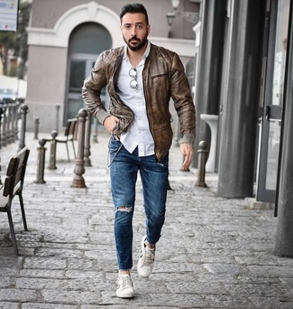How to wear: white low top sneakers, blue ripped skinny jeans, white long sleeve shirt, brown leather bomber jacket