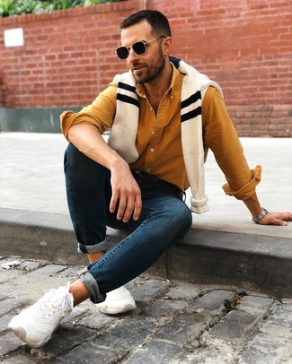 How to wear: white athletic shoes, navy skinny jeans, mustard long sleeve shirt, beige horizontal striped crew-neck sweater