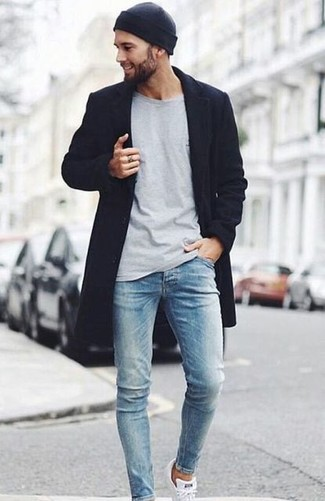 How to wear: white low top sneakers, light blue skinny jeans, grey long sleeve t-shirt, black overcoat