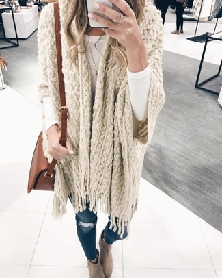 How to wear: beige suede ankle boots, navy ripped skinny jeans, white long sleeve t-shirt, beige knit poncho