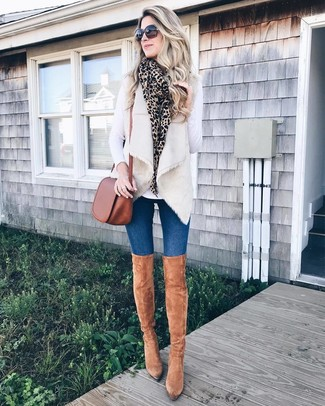 How to wear: tan suede over the knee boots, blue skinny jeans, white long sleeve t-shirt, beige fur vest