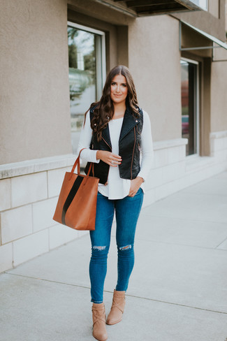 How to wear: tan leather ankle boots, blue ripped skinny jeans, white long sleeve t-shirt, black leather vest
