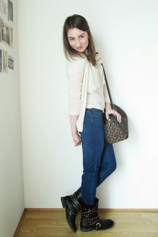 How to wear: black studded leather mid-calf boots, navy skinny jeans, beige sleeveless top, beige cardigan