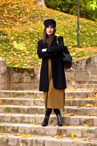 How to wear: black leather ankle boots, black skinny jeans, mustard sweater dress, black coat