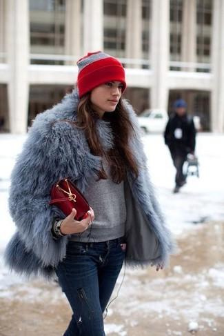 How to wear: red leather crossbody bag, navy ripped skinny jeans, grey sweatshirt, grey fur jacket