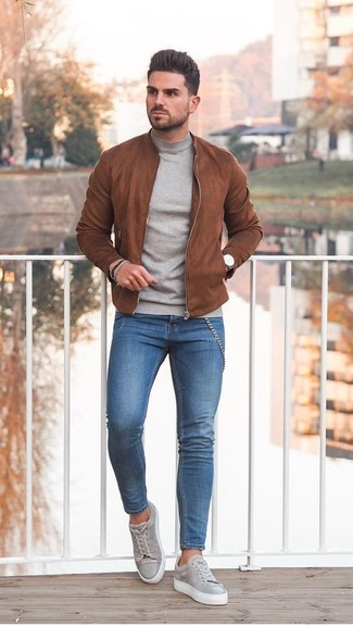 How to wear: grey suede low top sneakers, blue skinny jeans, grey turtleneck, tobacco suede bomber jacket