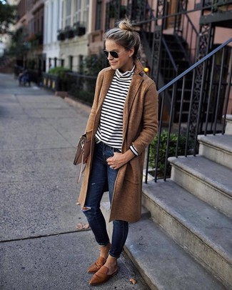 How to wear: brown leather loafers, navy ripped skinny jeans, white and black horizontal striped turtleneck, camel coat
