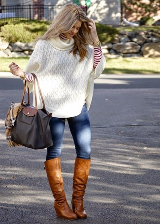 How to Wear Tan Leather Knee High Boots: This pairing of a white knit poncho and blue skinny jeans is impeccably stylish and yet it looks laid-back enough and ready for anything. For something more on the classier end to complete your ensemble, introduce tan leather knee high boots to the mix.