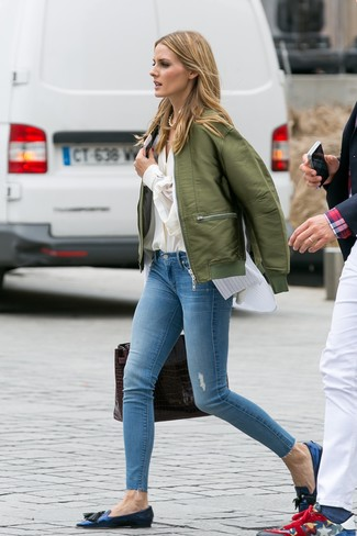 How to wear: light blue ripped skinny jeans, white vertical striped sleeveless button down shirt, beige button down blouse, olive bomber jacket