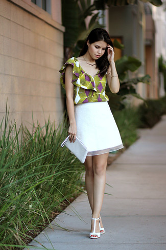 Make an army green print shell top and a white lace mini skirt your outfit choice for a glam and trendy getup. White leather heeled sandals will bring a classic aesthetic to the ensemble.