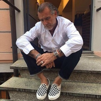 Fashion for Men Over 50: What To Wear: Consider wearing a white long sleeve shirt and navy jeans to put together a day-to-day look that's full of style and character. Introduce a pair of black and white check canvas slip-on sneakers to the mix and off you go looking dashing. This outfit shows that even after fifty you still have a wide array of styling options.