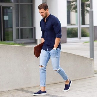 How to wear: brown leather zip pouch, navy slip-on sneakers, light blue ripped skinny jeans, navy long sleeve shirt