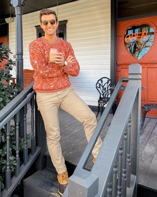 How to wear: brown sunglasses, tan snow boots, khaki chinos, orange cable sweater