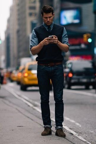How to wear: black sweater vest, blue denim shirt, navy jeans, dark brown suede desert boots