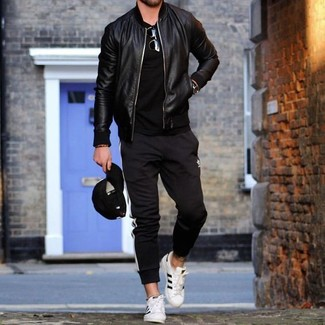 How to wear: white leather low top sneakers, black and white vertical striped sweatpants, black crew-neck t-shirt, black leather bomber jacket