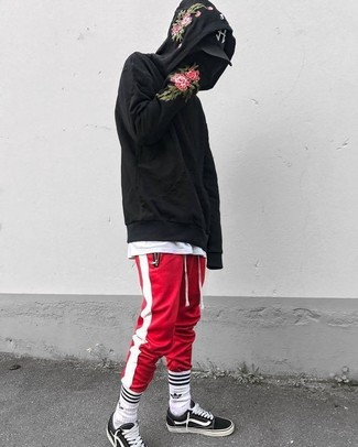 How to wear: black and white canvas low top sneakers, red and white vertical striped sweatpants, white crew-neck t-shirt, black floral hoodie