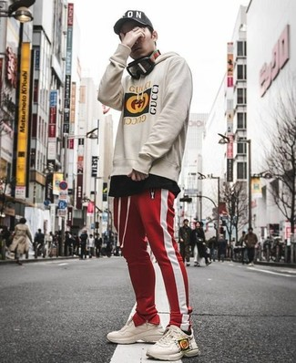 How to wear: beige leather athletic shoes, red and white vertical striped sweatpants, black crew-neck t-shirt, beige print hoodie