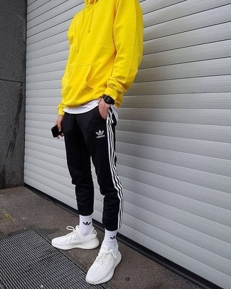 How to wear: white athletic shoes, black and white vertical striped sweatpants, white crew-neck t-shirt, yellow hoodie