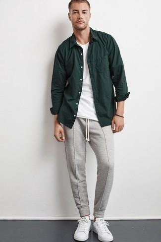 How to Wear Grey Sweatpants For Men: Combining a dark green long sleeve shirt with grey sweatpants is an awesome choice for a laid-back and cool ensemble. Let your outfit coordination credentials really shine by rounding off this outfit with a pair of white leather low top sneakers.
