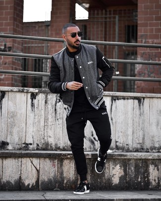How to wear: black and white leather low top sneakers, black sweatpants, black crew-neck t-shirt, charcoal varsity jacket