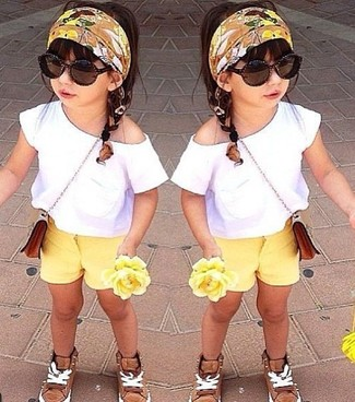 How to Wear Beige Sneakers For Girls: People will drool all over your child if she is dressed in this combo of a white t-shirt and yellow shorts. Complete this getup with beige sneakers.