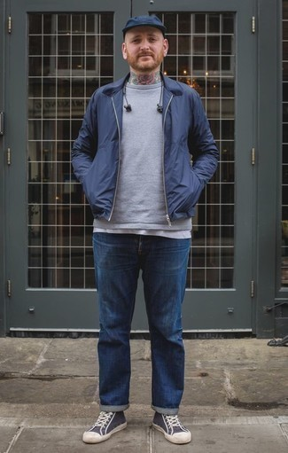 How to Wear a Navy Harrington Jacket: This laid-back pairing of a navy harrington jacket and blue jeans is very easy to throw together in next to no time, helping you look seriously stylish and prepared for anything without spending too much time searching through your wardrobe. Serve a little mix-and-match magic by rounding off with a pair of navy and white canvas high top sneakers.