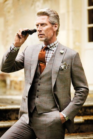 How to wear: brown plaid three piece suit, white and brown gingham dress shirt, orange tie, grey pocket square