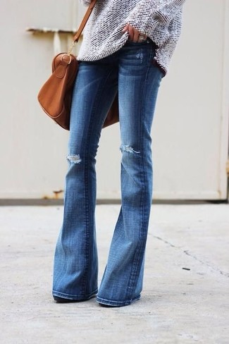 How to wear: tobacco leather duffle bag, blue ripped flare jeans, beige knit oversized sweater