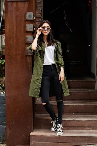 An olive trenchcoat and black ripped skinny jeans is a versatile combination that will provide you with variety. Take your ensemble into a more casual direction with black and white high top sneakers. It goes without saying that this one makes for a great, spring-ready ensemble.