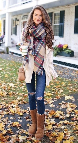 How to wear: beige leather crossbody bag, brown uggs, navy ripped skinny jeans, beige knit open cardigan