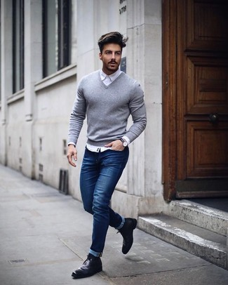 How to wear: grey v-neck sweater, white dress shirt, blue skinny jeans, black leather chelsea boots