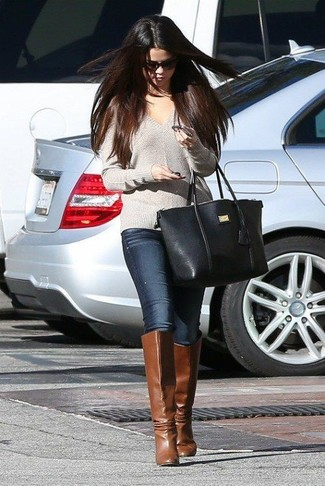 Selena Gomez wearing Grey V-neck Sweater, Navy Skinny Jeans, Brown Leather Knee High Boots, Black Leather Tote Bag