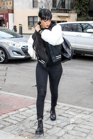 How to wear: black and white varsity jacket, black hoodie, black skinny jeans, black leather lace-up flat boots