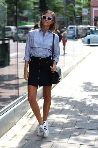 How to wear: black leather crossbody bag, white and black leather low top sneakers, black button skirt, light blue vertical striped dress shirt