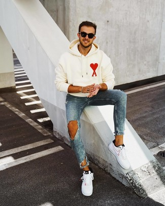How to Wear White and Black Leather Low Top Sneakers For Men: Marry a white print hoodie with blue ripped skinny jeans for relaxed dressing with an urban spin. If you want to feel a bit more refined now, complete this ensemble with a pair of white and black leather low top sneakers.