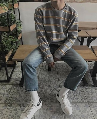 How to Wear White and Black Leather Low Top Sneakers For Men: If you appreciate the comfort look, marry a grey horizontal striped sweatshirt with light blue jeans. Let your outfit coordination chops really shine by finishing off your ensemble with a pair of white and black leather low top sneakers.
