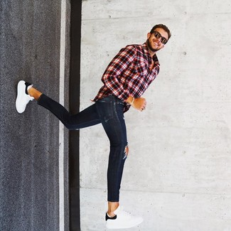How to Wear White and Black Leather Low Top Sneakers For Men: Stay stylish on lazy days in a red and black plaid long sleeve shirt and navy ripped skinny jeans. Take this ensemble a more sophisticated path by rounding off with white and black leather low top sneakers.