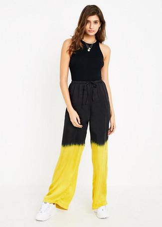 How to wear: gold pendant, white athletic shoes, yellow tie-dye wide leg pants, black tank