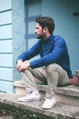How to Wear a Blue Dress Shirt For Men: A blue dress shirt and beige chinos are robust sartorial weapons in any man's wardrobe. You could perhaps get a little creative when it comes to footwear and complete your outfit with a pair of white canvas high top sneakers.