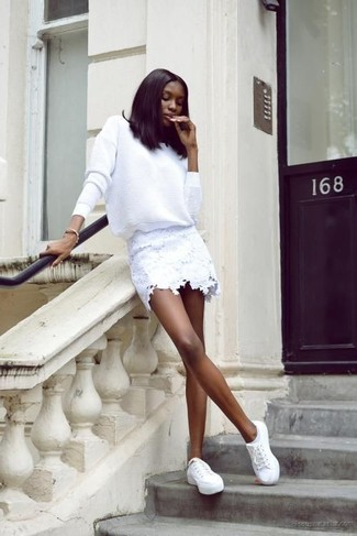 Reach for a white crew-neck jumper and a white lace mini skirt to achieve a chic look. Finish off your look with white low top sneakers.