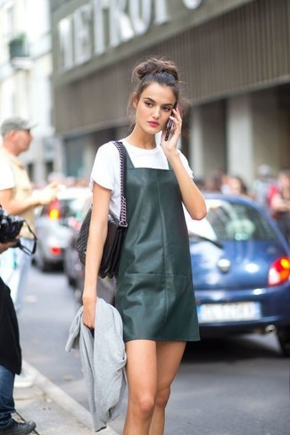 How to wear: black quilted leather satchel bag, white crew-neck t-shirt, dark green leather overall dress, grey bomber jacket