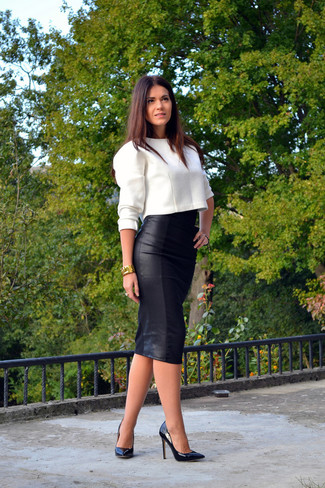 A white cropped sweater and a black leather midi skirt is a great combination worth integrating into your wardrobe. Black leather pumps will bring a classic aesthetic to the ensemble.