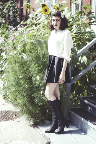 A white knit cropped sweater and a black leather skater skirt is a nice combo to add to your casual lineup. Elevate this ensemble with black leather knee high boots.
