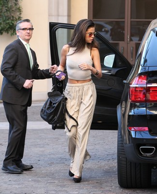 Selena Gomez wearing White Cropped Top, Beige Wide Leg Pants, Black Suede Pumps, Black Leather Satchel Bag