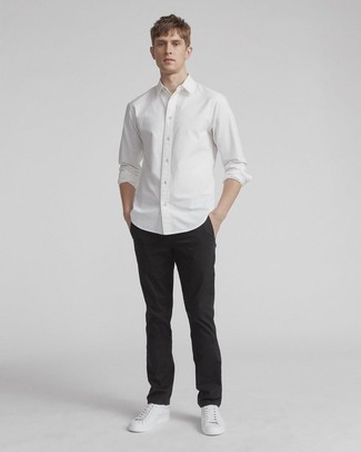 How to Wear Black Chinos: Showcase your prowess in menswear styling by combining a white long sleeve shirt and black chinos for a casual combination. A pair of white leather low top sneakers will bring a laid-back vibe to this getup.