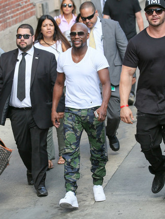 This contemporary combo of a white v-neck t-shirt and green camouflage sweatpants is very easy to pull together without a second thought, helping you look seriously stylish and prepared for anything without spending a ton of time searching through your closet. And if you need to effortlesslly step up this ensemble with one piece, why not complete this ensemble with a pair of white leather low top sneakers?