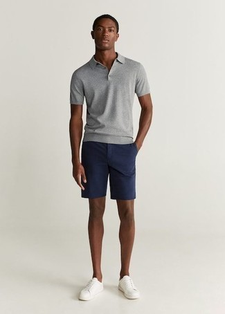 Men's Looks & Outfits: What To Wear In Summer: A grey polo and navy shorts are must-have menswear essentials if you're piecing together an off-duty closet that matches up to the highest sartorial standards. Introduce a pair of white leather low top sneakers to the mix et voila, this getup is complete. This here is proof that it is indeed possible to survive the crazy heat, all while looking fresh and breezy.