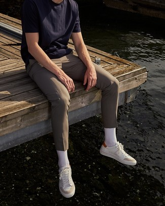How to Wear Beige Chinos: For a look that's pared-down but can be styled in plenty of different ways, go for a navy crew-neck t-shirt and beige chinos. Now all you need is a pair of white leather low top sneakers to complement your look.