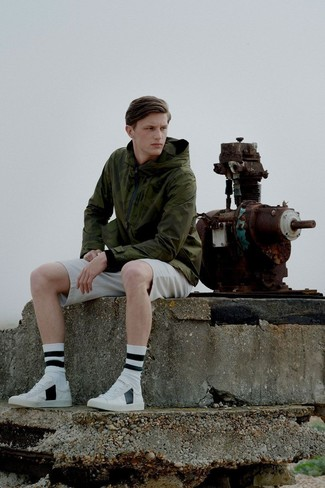 How to wear: white and black horizontal striped socks, white leather low top sneakers, beige shorts, olive windbreaker